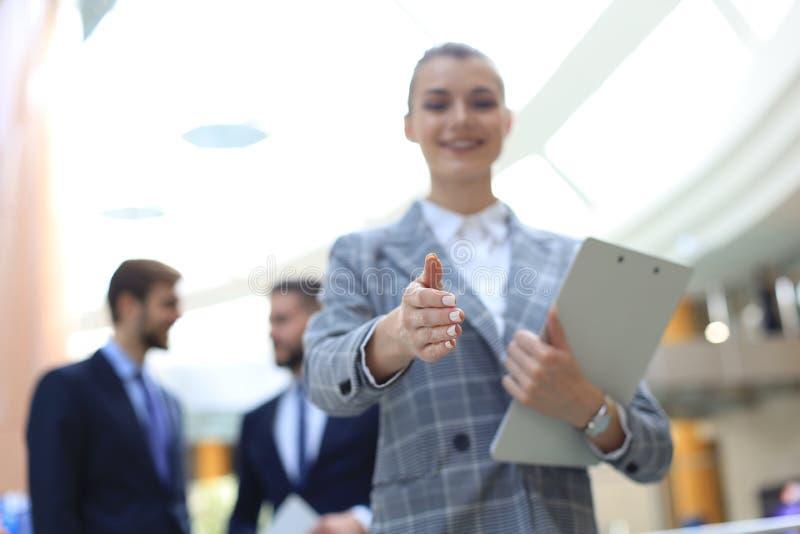 Mujer con una mano abierta lista para el apret?n de manos en oficina fotos de archivo