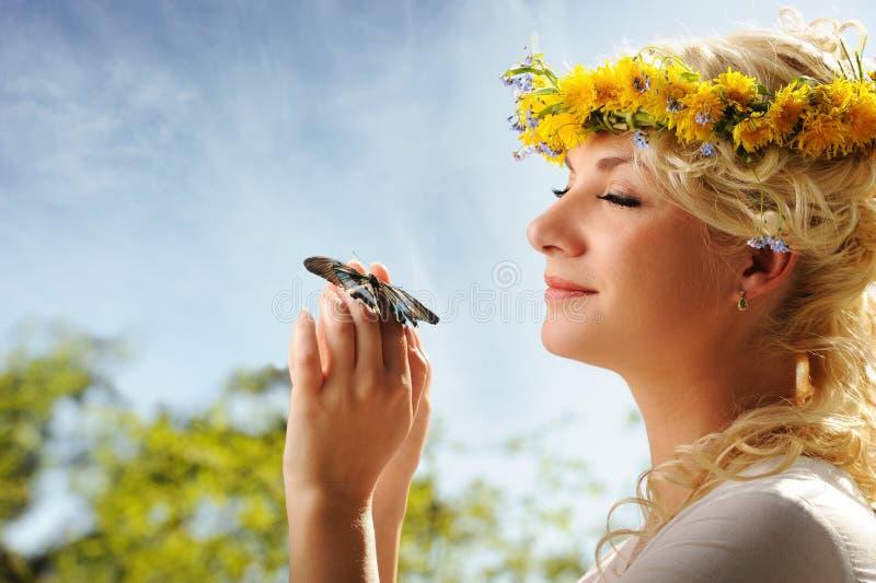 mujer con una mariposa sobre el cielo azul fotos de archivo