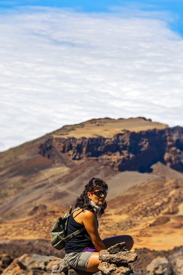 Mujer con una mochila que se sienta al borde del acantilado en los vagos fotografía de archivo libre de regalías