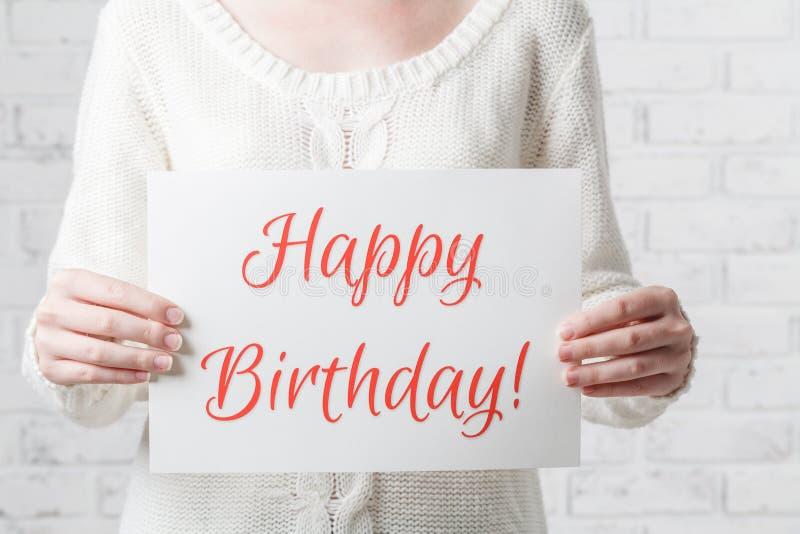 Mujer con una muestra en sus manos con el feliz cumpleaños de las palabras imagen de archivo