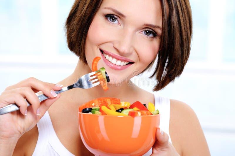 Mujer con una placa de la ensalada vegetal en manos