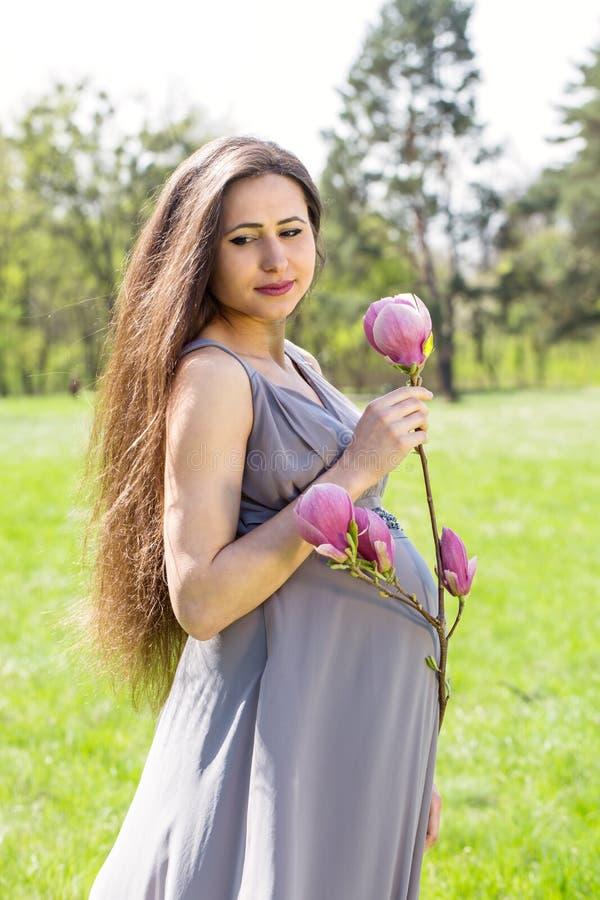 Mujer con una rama de la magnolia fotos de archivo