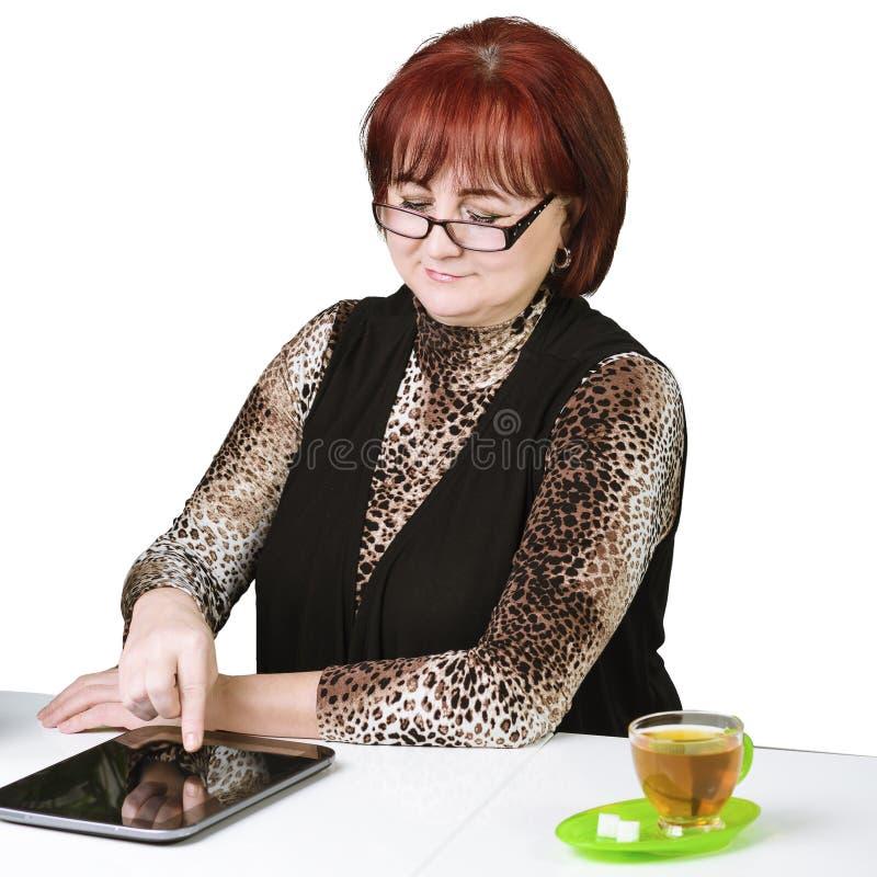 Mujer con una tableta en la tabla en un fondo blanco fotos de archivo