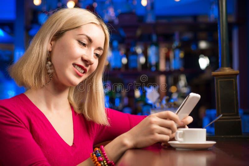 Mujer con una taza de café y de teléfono celular foto de archivo