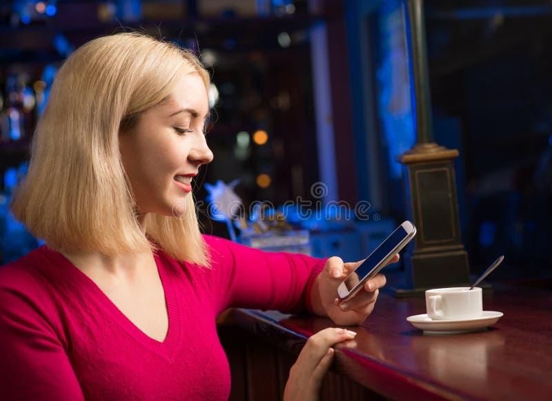 Mujer con una taza de café y de teléfono celular imagen de archivo libre de regalías