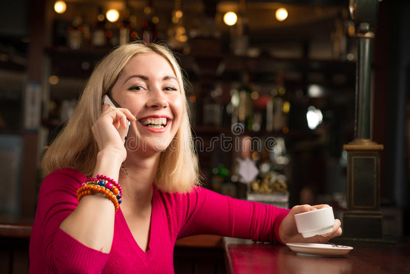 Mujer con una taza de café y de teléfono celular imagen de archivo