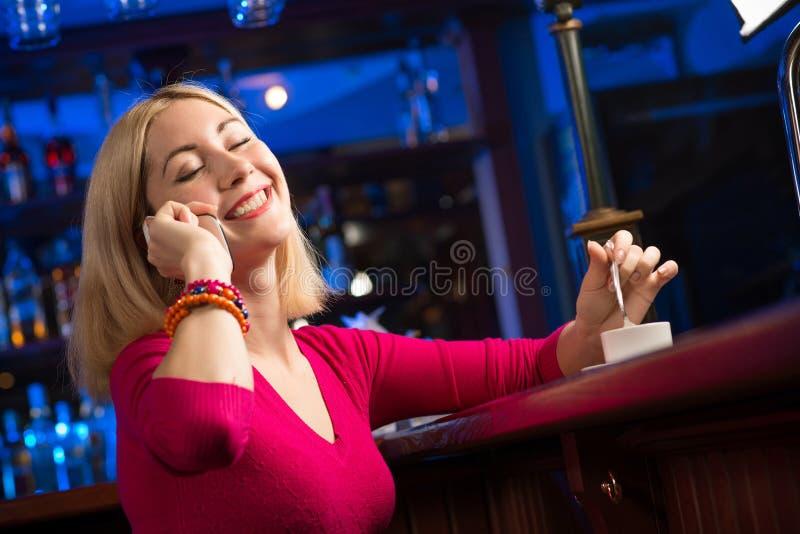 Mujer con una taza de café y de teléfono celular foto de archivo libre de regalías
