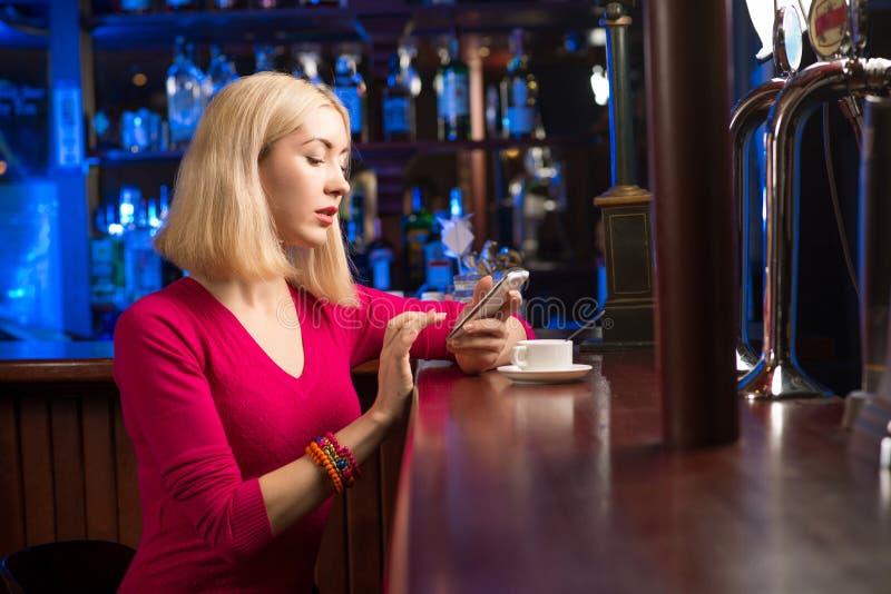 Mujer con una taza de café y de teléfono celular fotos de archivo libres de regalías