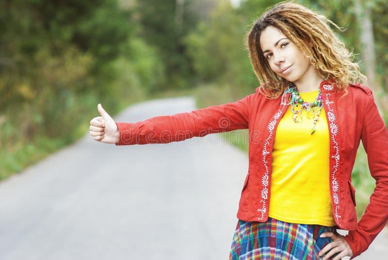 Mujer con votos de los dreadlocks que hace autostop imagen de archivo