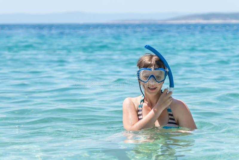 Mujer con zambullida de la máscara que bucea en el mar imagenes de archivo