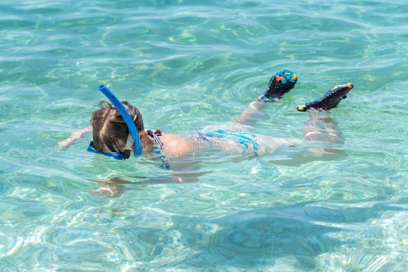 Mujer con zambullida de la máscara que bucea en el mar imagen de archivo
