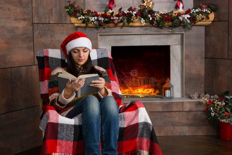 Mujer concentrada atractiva en whi divertido de la lectura del sombrero de la Navidad fotografía de archivo