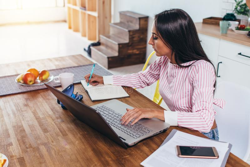 Mujer concentrada del freelancer que hace notas de Internet que trabaja a casa sentarse en la tabla fotografía de archivo