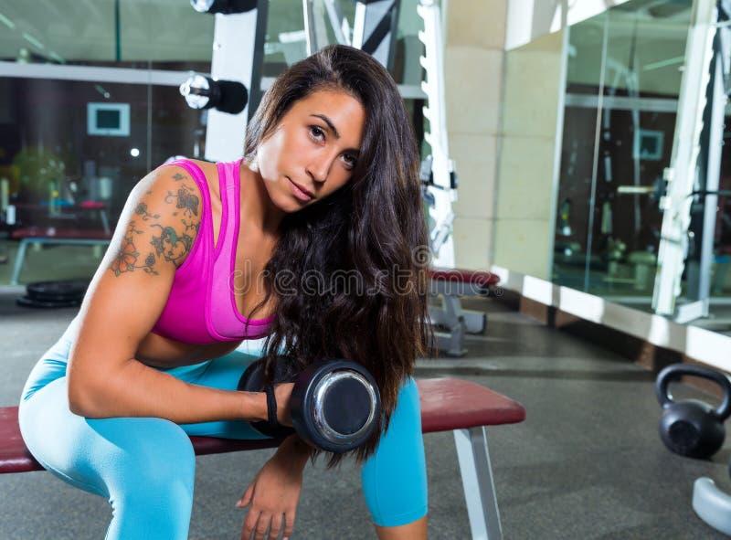 Mujer concentrada pesa de gimnasia de la muchacha del rizo del bíceps imagen de archivo libre de regalías