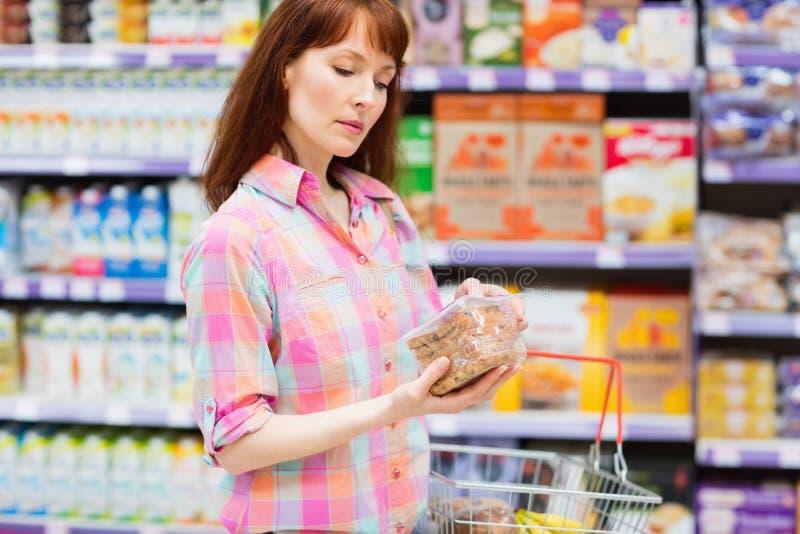 Mujer concentrada que elige cuidadosamente un producto foto de archivo libre de regalías