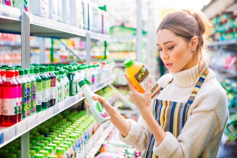 Mujer concentrada que elige las sustancias químicas agrícolas para las flores y las plantas fotografía de archivo libre de regalías
