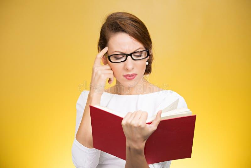 Mujer concentrada que piensa en contenido del libro imagenes de archivo