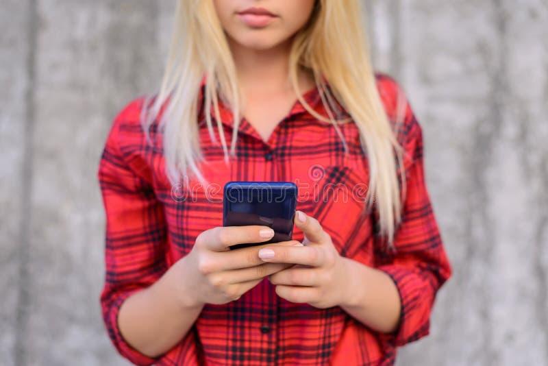 Mujer concentrada, tranquila que mecanografía y que consigue mensajes en su uso móvil de la mano del mensaje del SMS del teléfono foto de archivo libre de regalías