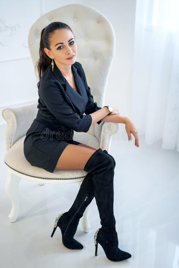 Mujer confiada elegante hermosa que se sienta en una silla blanca en el estudio fotografía de archivo libre de regalías