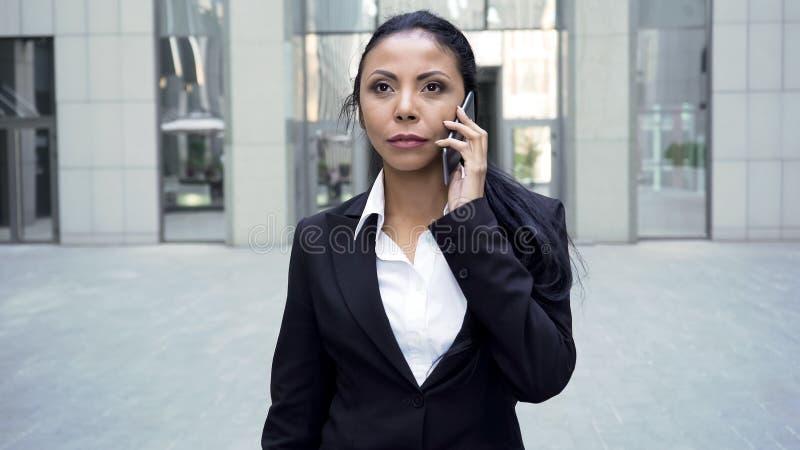 Mujer confiada en caminar del traje de negocios, celebrando el teléfono por el oído, conversación imagen de archivo libre de regalías