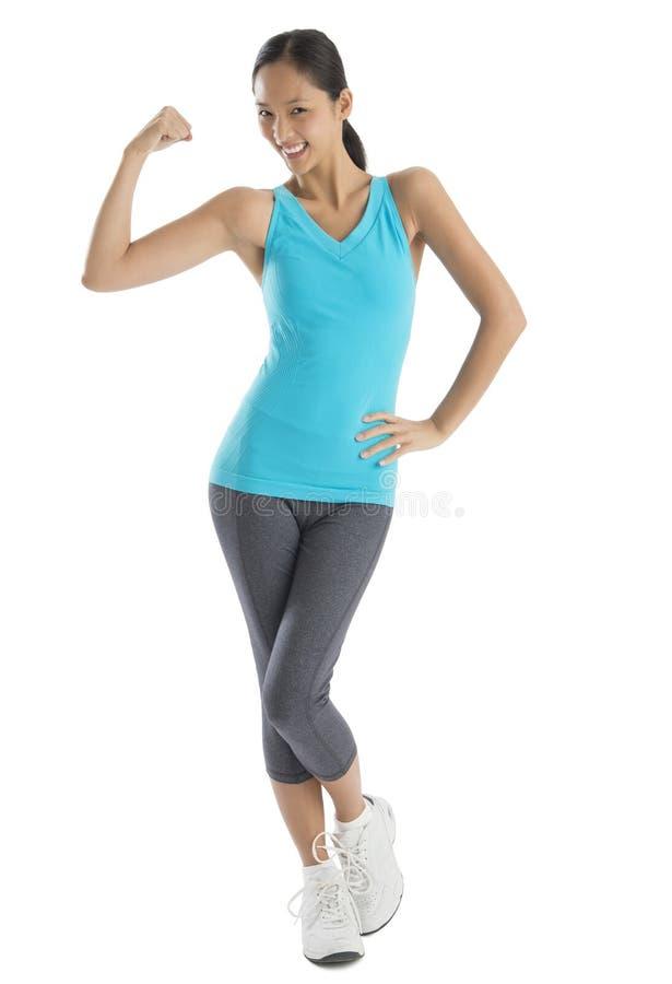 Mujer confiada en la ropa de los deportes que dobla los músculos fotos de archivo