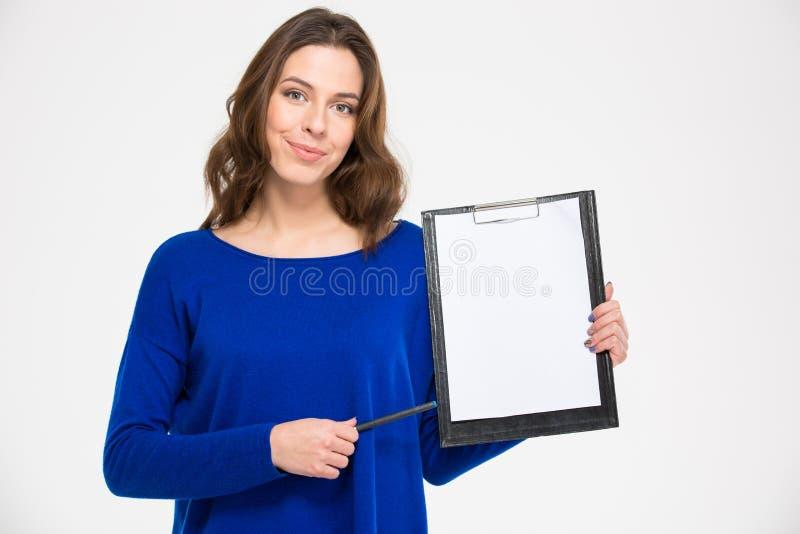 Mujer confiada sonriente que sostiene el tablero y que señala en él foto de archivo