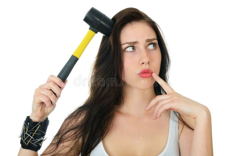 Mujer confusa con martillo cerca de la cabeza imagenes de archivo
