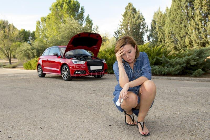 Mujer confusa desesperada trenzada con el accidente quebrado del desplome del motor de coche que invita al teléfono móvil fotografía de archivo