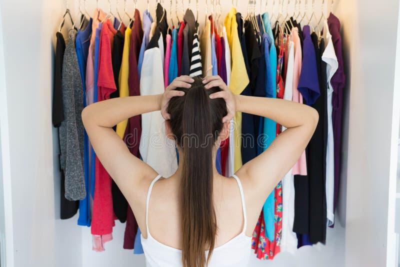 Mujer confusa que elige qué llevar delante de su guardarropa imágenes de archivo libres de regalías