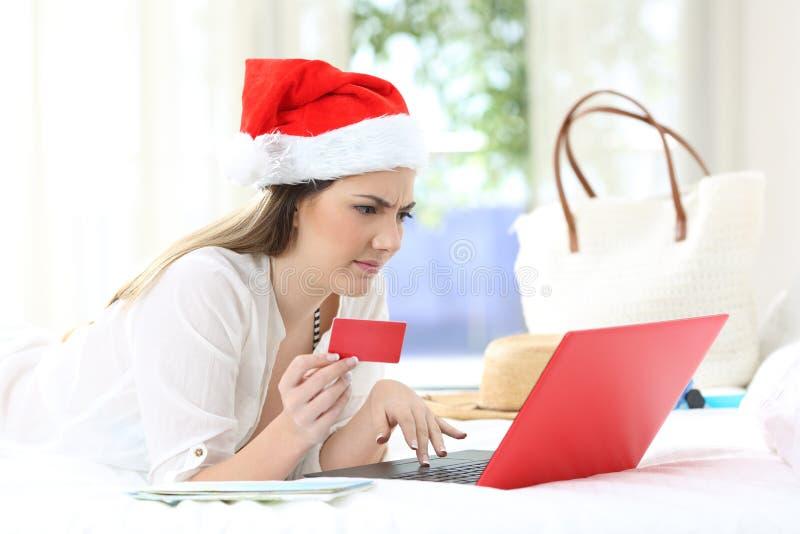 Mujer confusa que paga en línea el días de fiesta de la Navidad imágenes de archivo libres de regalías