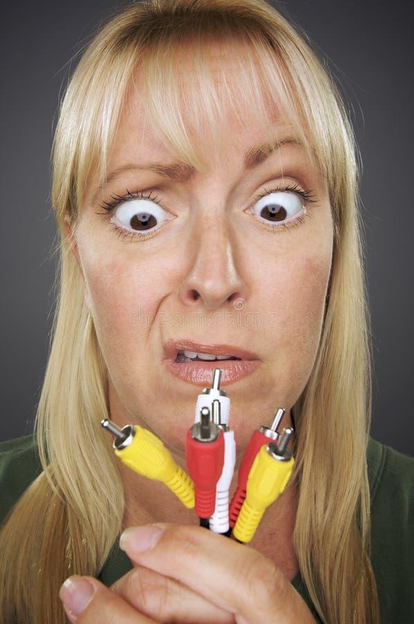 Mujer confusa que sostiene los cables electrónicos fotos de archivo libres de regalías