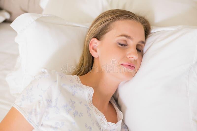Mujer contenta natural que duerme en cama imagen de archivo