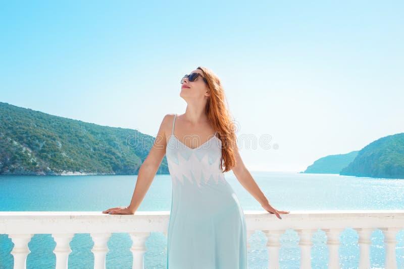 Mujer contenta que se enfría en terraza tropical imagen de archivo libre de regalías