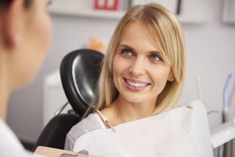 Mujer contenta y sonriente en la cl?nica del dentista imagen de archivo