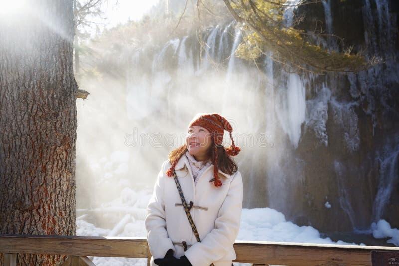 Mujer contra la cascada congelada imagen de archivo