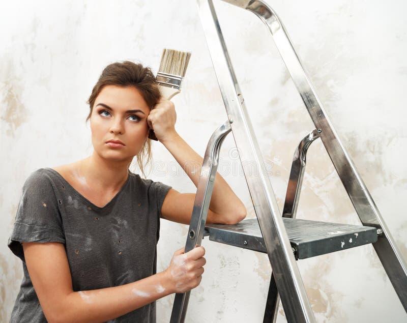 Mujer contrariedad con la escalera y el cepillo fotografía de archivo libre de regalías