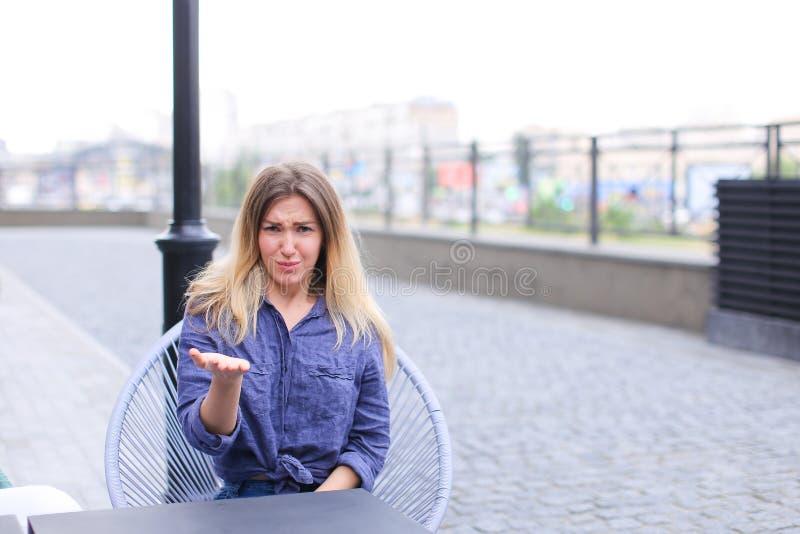 Mujer contrariedad joven que se sienta en el café de la calle y que hace caras fotos de archivo libres de regalías