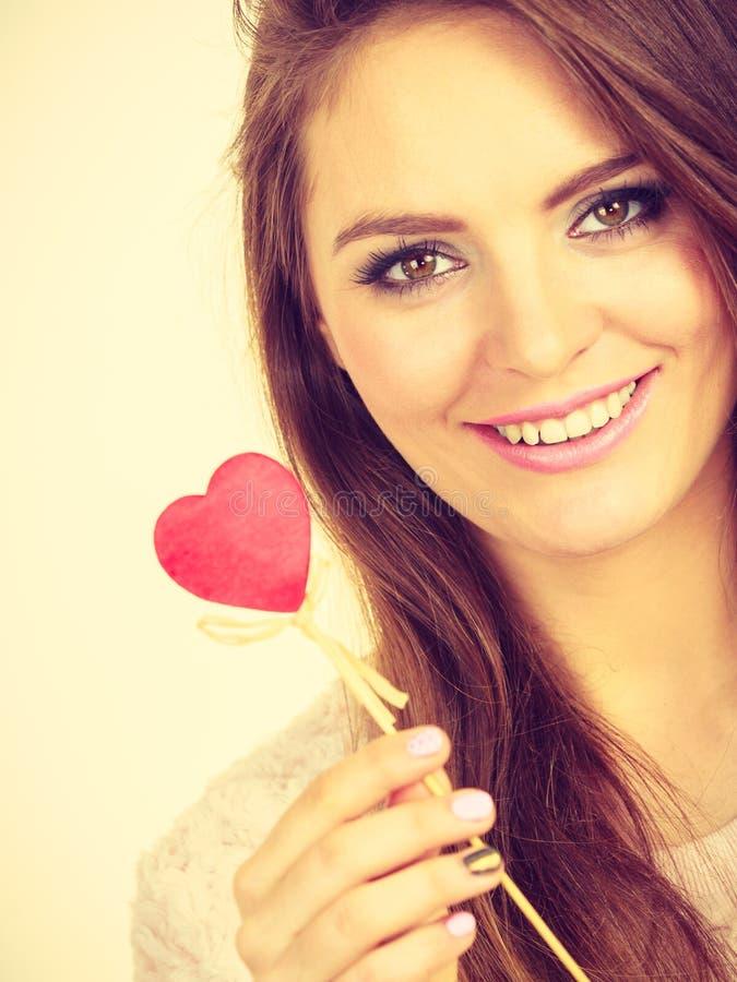 Mujer coqueta que lleva a cabo el coraz?n de madera rojo en el palillo imagen de archivo libre de regalías