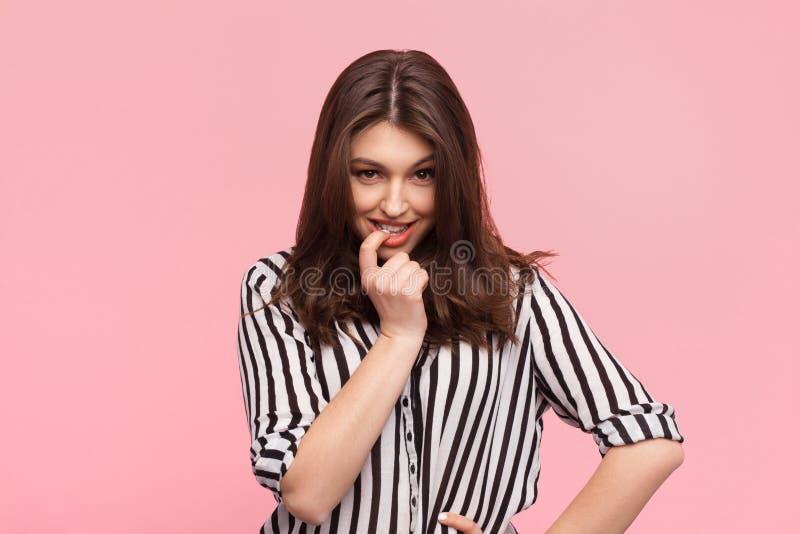 Mujer coqueta que presenta en rosa imagenes de archivo