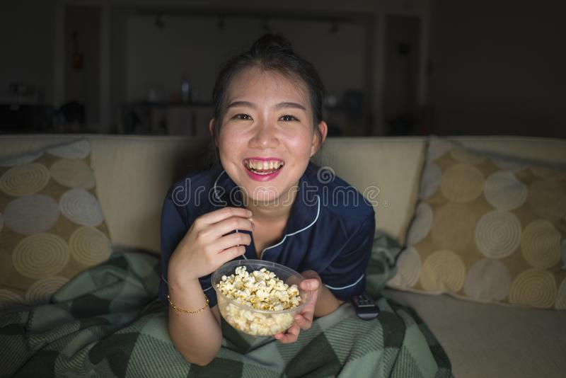 Mujer coreana asiática feliz y alegre hermosa joven que mira la película de la comedia de la TV o la demostración hilarante que r imagenes de archivo