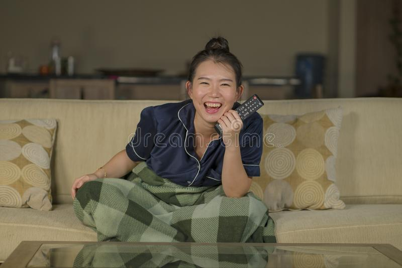 Mujer coreana asiática feliz y alegre hermosa joven que mira la película de la comedia de la TV o la demostración hilarante que r fotos de archivo libres de regalías