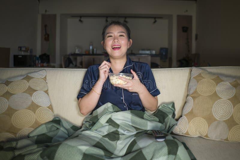 Mujer coreana asiática feliz y alegre hermosa joven que mira la película de la comedia de la TV o la demostración hilarante que r imagen de archivo libre de regalías