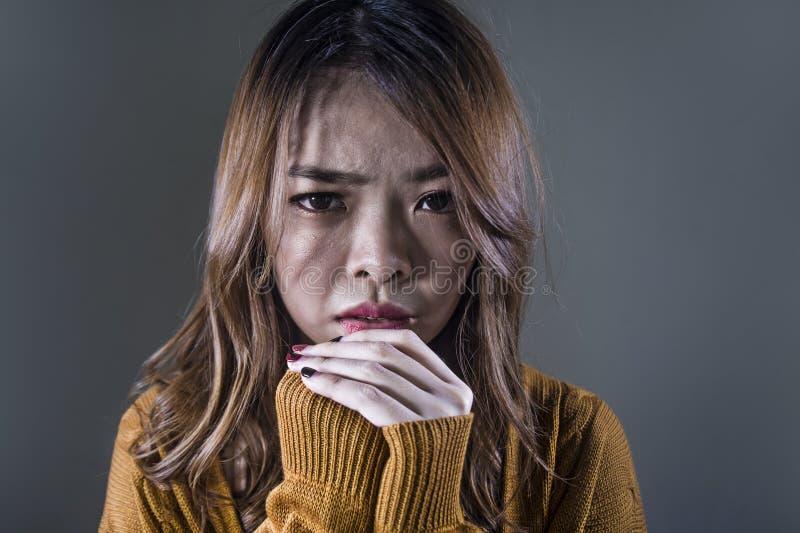 Mujer coreana asiática triste y desesperada que mira la sensación deprimida desamparada y el dolor en fondo oscuro aislado en car imagenes de archivo