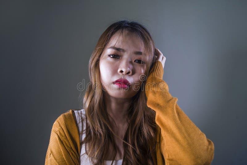 Mujer coreana asiática triste y desesperada que mira la sensación deprimida desamparada y el dolor en fondo oscuro aislado en car imagen de archivo libre de regalías