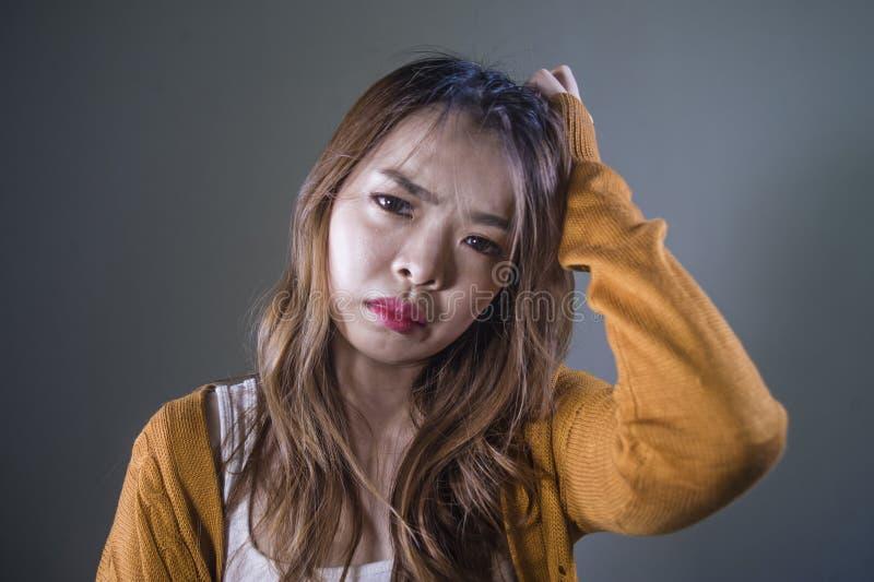 Mujer coreana asiática triste y desesperada que mira la sensación deprimida desamparada y el dolor en fondo oscuro aislado en car fotografía de archivo libre de regalías