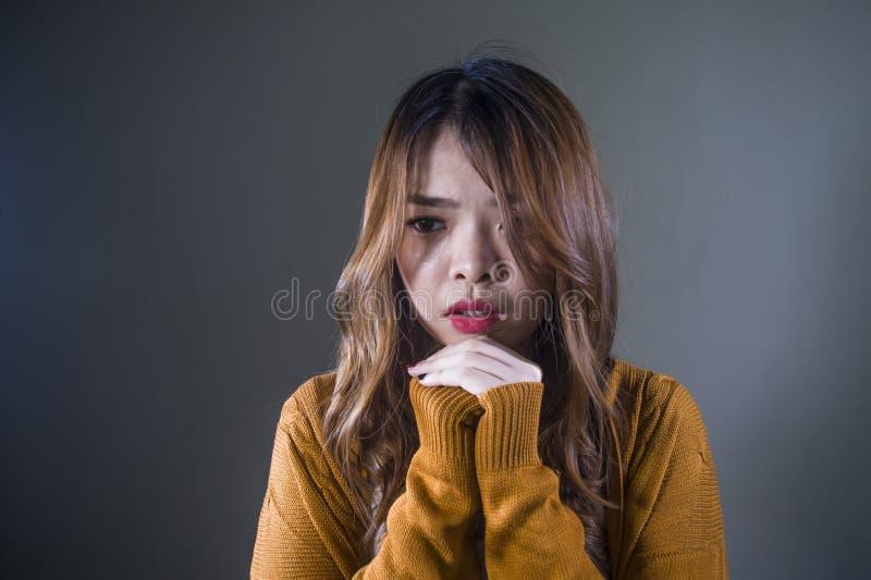Mujer coreana asiática triste y desesperada que mira la sensación deprimida desamparada y el dolor en fondo oscuro aislado en car fotos de archivo libres de regalías