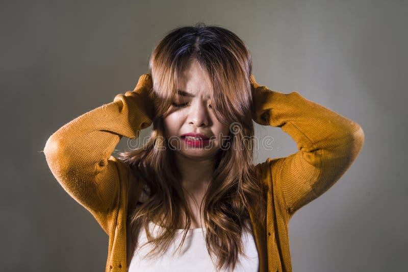 Mujer coreana asiática triste y desesperada que mira la sensación deprimida desamparada y el dolor en fondo oscuro aislado en car imágenes de archivo libres de regalías