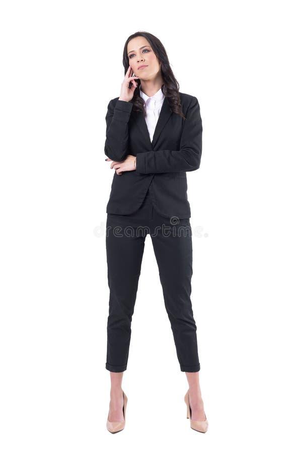 Mujer corporativa atenta atenta en el traje de negocios que parece para arriba interesado durante la presentación imagen de archivo