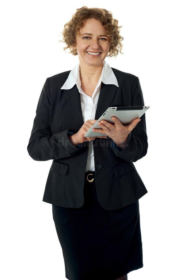 Mujer corporativa cabelluda rizada que presenta con el ipad foto de archivo libre de regalías