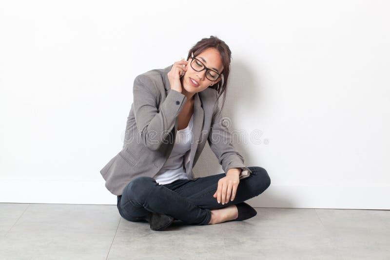 Mujer corporativa joven que habla en su teléfono celular en el piso fotografía de archivo